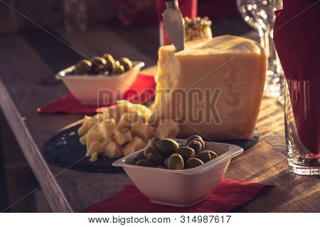 Wooden Table With Parmesan Cheese And Olives Food. Healthy Food. Catering Food. Plate Of Parmesan An