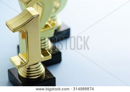 1st, 2nd And 3rd Place Gold Winners Trophies With Three Dimensional Metallic Numbers Arranged In A R