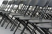 numerous folding chairs arranged in a row in a conference room. poster