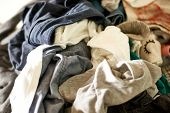 Close up on a big pile of clothes and accessories thrown on the ground. Untidy cluttered poster