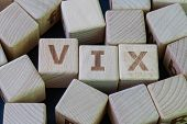 Volatility Index, known by its ticker symbol VIX concept, cube wooden block with alphabet combine the word VIX on black chalkboard background. poster