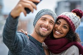 Happy multiethnic couple in the city taking photo in a winter day. Smiling man and african girl taking selfie with smartphone on street. Young woman and cheerful guy on christmas holidays.