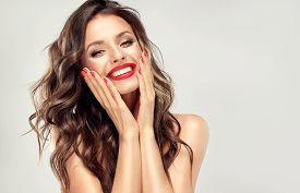 Woman With Red Lips And Nails With Smile Surprise Holds Cheeks By Hand .beautiful Girl  With Curly H