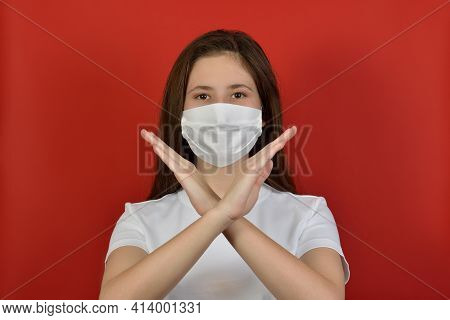 Portrait Of A Serious Brunette Girl, In A White Mask And A White T-shirt, Gesturing With Crossed Arm