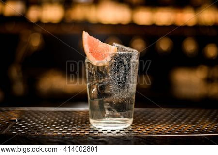 Glass With Cold Carbonated Drink Decorated With Slice Of Grapefruit On Bar Counter