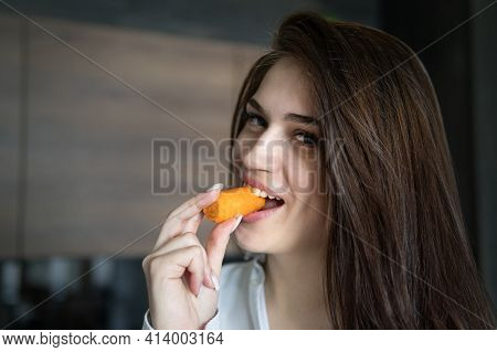 Close Up Of Woman Eating Nibbling Carrot And Smiling In The Kitchen Interior.. Health Diet Food. Nib