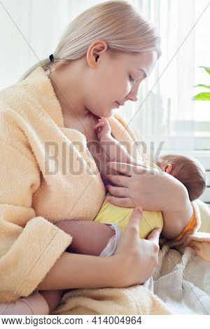 Baby Eating Breast Milk. Caucasian Blonde Young Mother Breastfeeding Her Baby At Home Vertical Photo