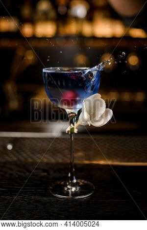 View On Transparent Glass With Splashing Blue Drink And Decorated With White Flower