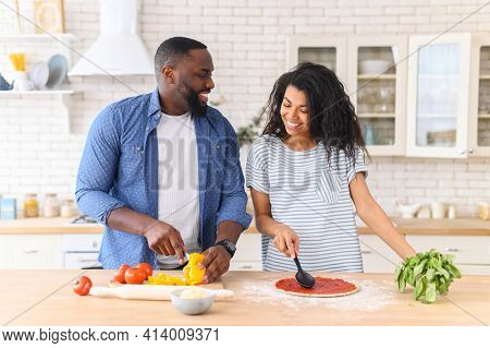 Romantic Couple Is Cooking On Kitchen. Handsome Man Cuts Vegetables And Attractive Young Woman Prepa