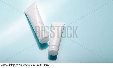 White Cosmetic Product In Tubes On Color Background With Water Drops. Mock Up Skincare Cosmetic Pack