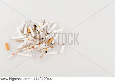 Plenty Of Cigarette Ends On White Surface, Ecology Concept, Top View.