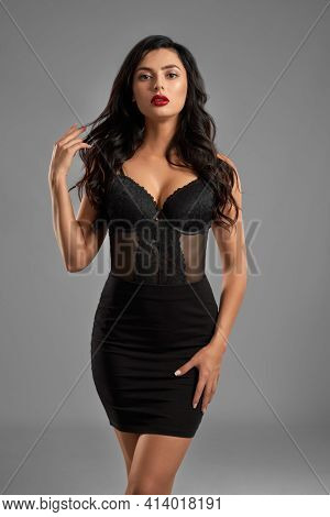 Adorable Young Woman With Dark Wavy Hair And Evening Makeup Posing Sexy In Studio. Charming Female W