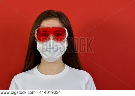 Portrait Of A Serious Pretty Cute Young Brunette Girl In A White Medical Mask, Red Safety Glasses Ov