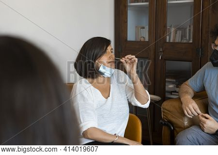 Caucasian Woman Sitting At A Living Room Of A House With People, Introducing A Nasal Swab In The Nos