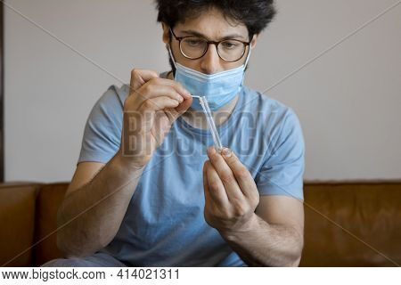 Young Man Sitting At Home Manipulating An Antigen Kit After Performing Self-swabbing Home Tests For