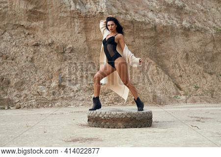 Glamorous Young Lady With Dark Wavy Hair And Bright Makeup Posing Among Desert On Old Car Tyre. Fash