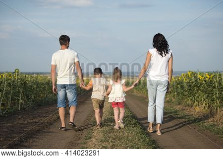 A Family Of Four People Mother, Father, Son And Daughter Walk In The Countryside Along A Field With