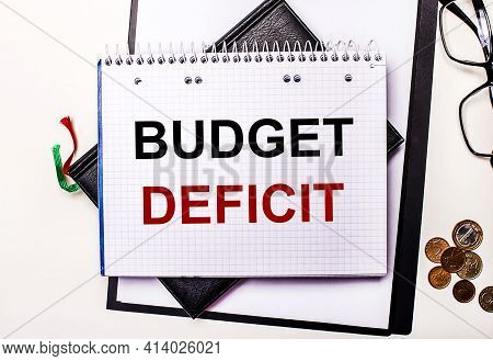 On A Light Background Glasses, Coins And A Notebook With The Inscription Budget Deficit. Business Co