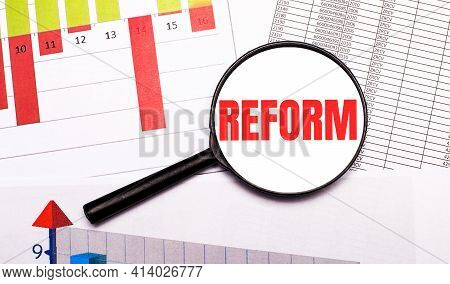 On The Desktop, Graphs, Reports, A Magnifying Glass With The Inscription Reform. Business Concept