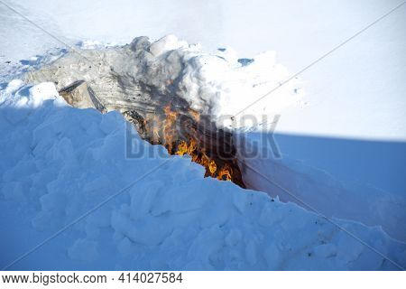 Burning Trash In The Snow. A Place For Incineration Of Household Waste In The Garden. Disposal Of Tr