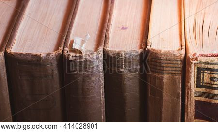 A Shelf With Ancient Books In Beautiful Bindings With Yellowed Pages.