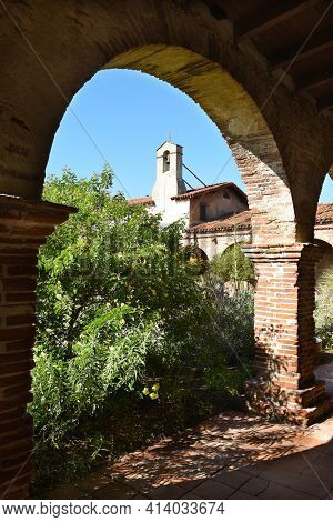 SAN JUAN CAPISTRANO, CA - DECEMBER 12, 2017: Mission San Juan Capistrano North Wing Bell Tower seen through the arches of the Serra Chapel.