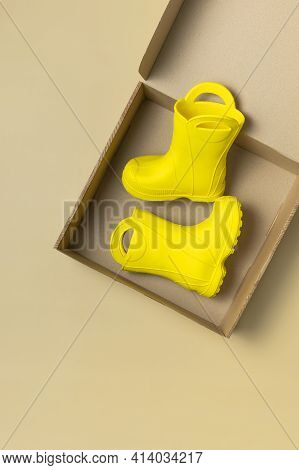 Baby Yellow Rubber Boots In Cardboard Craft Box On Beige Background. Waterproof Polymeric Footwear.