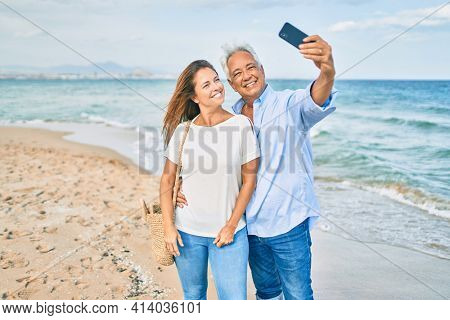 Middle age hispanic couple smiling happy making selfie by the smartphone at the beach.