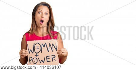 Middle age hispanic woman holding woman power banner scared and amazed with open mouth for surprise, disbelief face