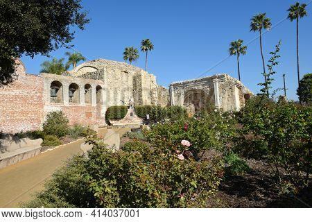 San Juan Capistrano, Ca - December 1, 2017: Mission Bell wall and Serra Statue with the Ruins of the Great Stone Church with rose garden in the foreground.