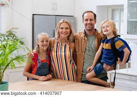 Portrait of smiling caucasian parents with son and daughter wearing school bags embracing in kitchen. happy family spending time together at home.