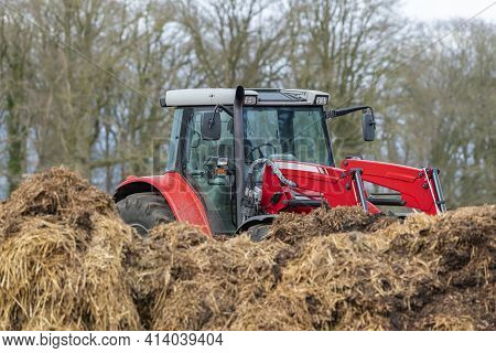 Red Tractor With Front Loader In Front Of A Manure Heap On A Field In The Achterhoek In The Netherla