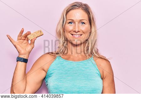 Middle age caucasian blonde woman eating protein bar as healthy energy snack looking positive and happy standing and smiling with a confident smile showing teeth
