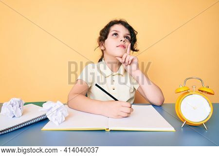 Cute hispanic child studying for school writing book sitting on the table serious face thinking about question with hand on chin, thoughtful about confusing idea