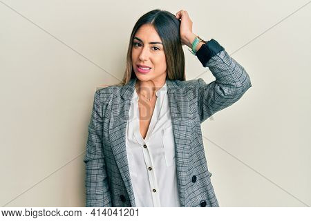 Young hispanic woman wearing business clothes confuse and wonder about question. uncertain with doubt, thinking with hand on head. pensive concept.