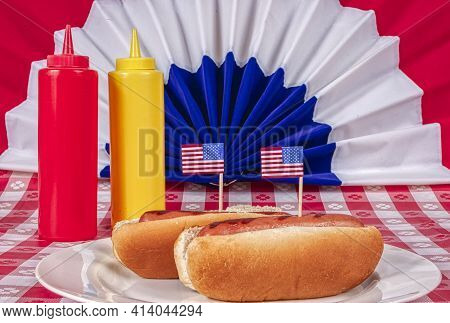 Horizontal Shot Of Two Patriotic Hot Dogs With American Flags.  This Is A Revised Image.