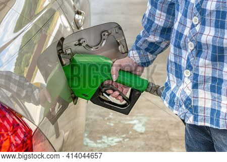 Horizontal Shot Of A Woman From The Right Below Shoulders Down Pumping Gas Into Her Car.