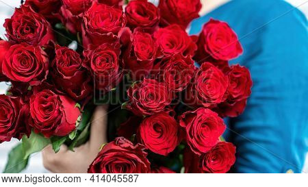 Luxurious Bouquet Of Red Roses Close Up. The Girl Is Holding A Large Bouquet Of Flowers In Her Hands