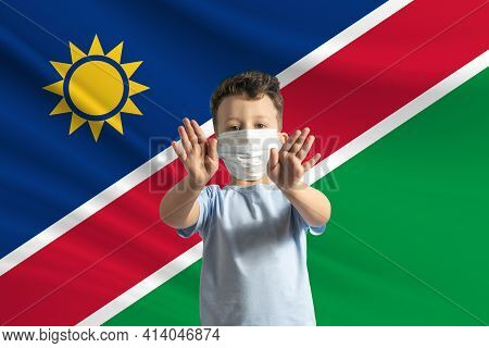 Little White Boy In A Protective Mask On The Background Of The Flag Of Namibia. Makes A Stop Sign Wi