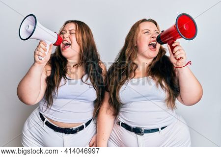 Plus size caucasian sisters woman shouting through megaphone angry and mad screaming frustrated and furious, shouting with anger. rage and aggressive concept.
