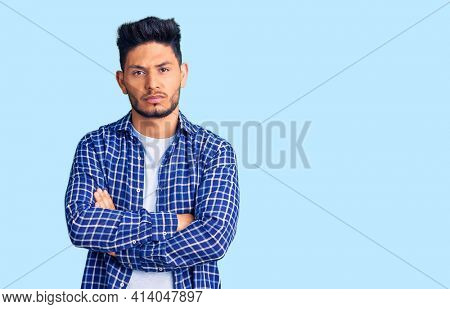 Handsome latin american young man wearing casual shirt skeptic and nervous, disapproving expression on face with crossed arms. negative person.