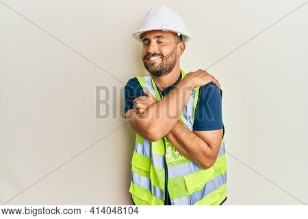 Handsome man with beard wearing safety helmet and reflective jacket hugging oneself happy and positive, smiling confident. self love and self care
