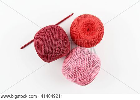 Crimson, Red And Pink Cotton Thread Balls And Crochet Hook On White Background. The Concept Of A Fav