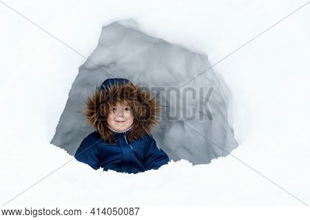 Chilld In A Winter Jacket With A Fur Collar Sits Inside An Ice House, An Igloo, A Shelter. Winter Ga