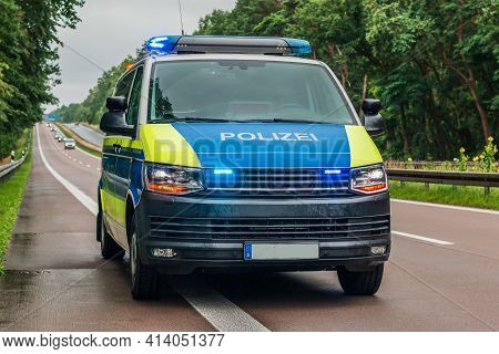 Police Car From Germany From The State Of Brandenburg On The Autobahn. Switched On Blue Light And Wa