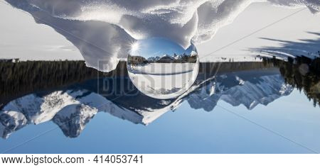 View Of A Scenic Snow Peaked Mountain Range In A Lens Ball With The Mountain Range Inverted In Behin
