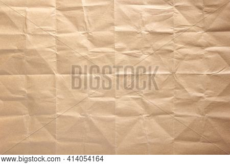 Wrinkled paper texture as background texture. Folded brown craft paper
