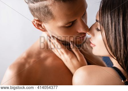Young Woman Kissing Sensual Boyfriend On Blurred Background.
