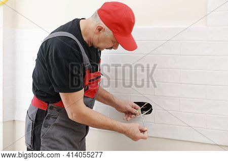 Electrician Hands Tighten Electrical Wires In Wall Fixture Or Socket Using A Screw Driver - Closeup.