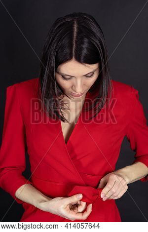 Beautiful Middle-aged Woman Fasten Belt With A Bow On Red Dress. Dark Hair, Slim Shape, Black Backgr